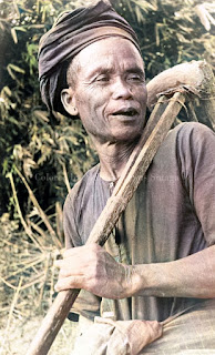 pria dewasa suku batak toba menggendong cangkul pacul patjol