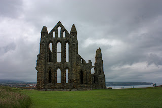Photo of Whitby Abbey against a very cloudy sky, giving a moody atmosphere.