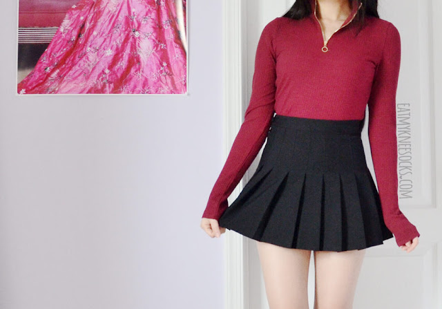 Details on the wine red/burgundy ribbed long-sleeve mock neck top from SheIn, a style similar to the UNIF Noob bodysuit, worn with an American Apparel dupe pleated black tennis skirt.