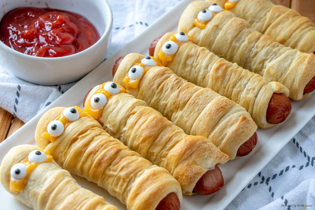 Hot dogs wrapped in crescent rolls with eyes on white platter with a ketchup on the side