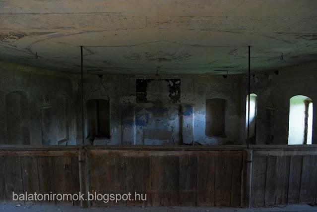 Rálátás a zsinagóga belső, festett falaira a női karzatról. Előtérben fakorlát.