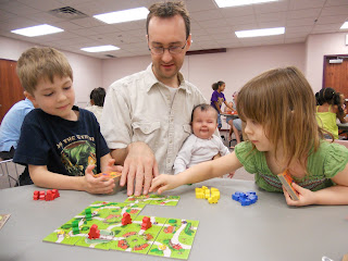 A man sits at a table with two children who appear to be in kindergarten or first grade, playing a board game with them. The game is a modular board made up of tiles containing roads through grassy fields, and the players are placing brightly coloured plastic pieces on the board.