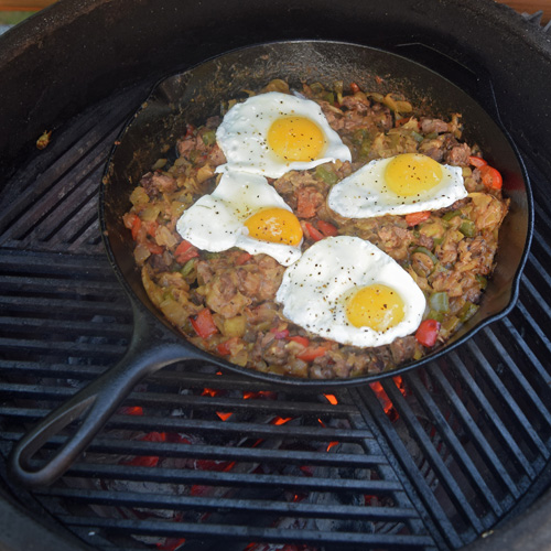 Steak and cheese breakfast hash in a cast iron skillet