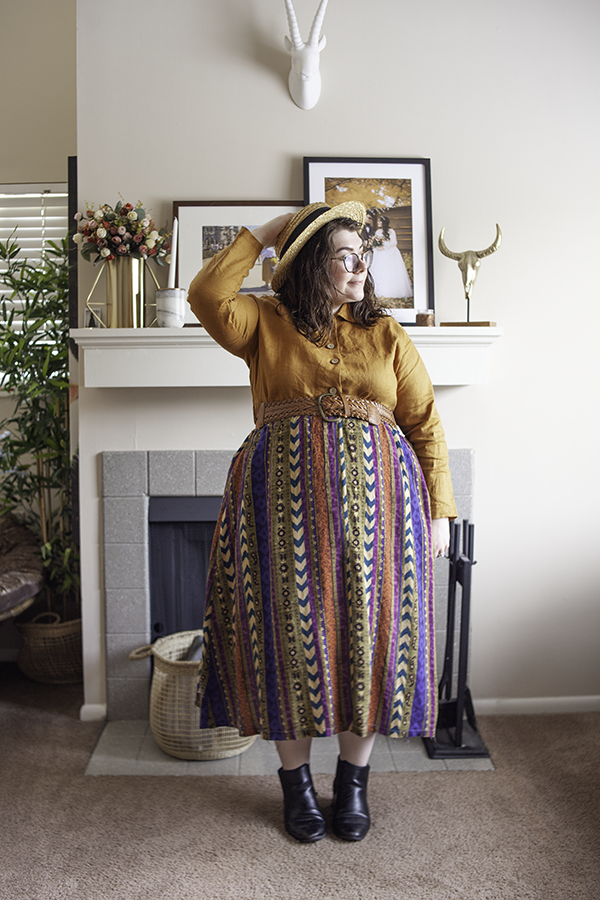 An outfit consisting of a straw boater hat, a golden brown collared button down long sleeve linen dress, worn as a blouse, a patterned maxi skirt and black Chelsea Boots.