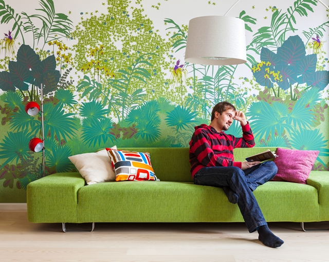 Photo of person reading a book on the green sofa