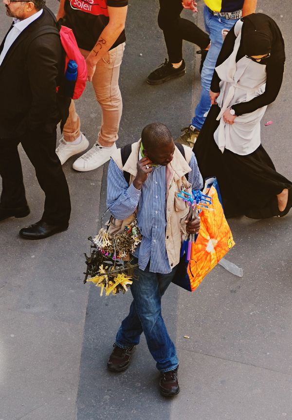 A souvenir seller with his collection of Eiffel Tour and selfie sticks, metro Bir-Hakeim. Paris photos by Kent Johnson for Street Fashion Sydney.
