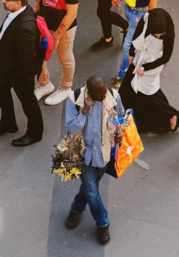 A souvenir seller with his collection of Eiffel Tour and selfie sticks, metro Bir-Hakeim. Paris photos by Kent Johnson for Street Fashion Sydney.
