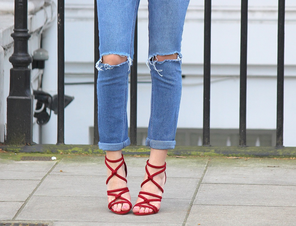 peexo fashion blogger wearing ripped mom jeans and red strappy heels in spring