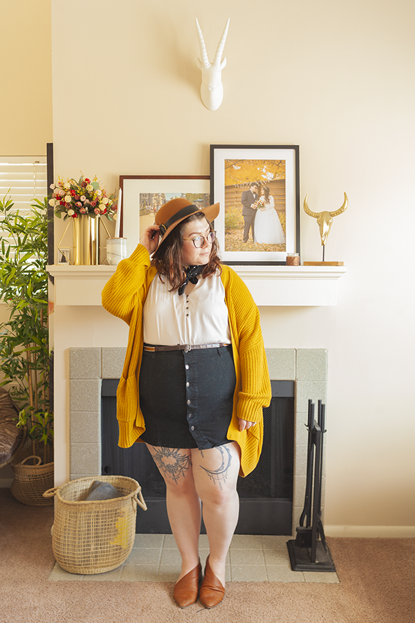 An outfit consisting of a brown panama hat, black dotted neck scarf, mustard yellow chunky cardigan over a whit v neck sleeveless blouse tucked into a black button skirt and brown d'orsay flats