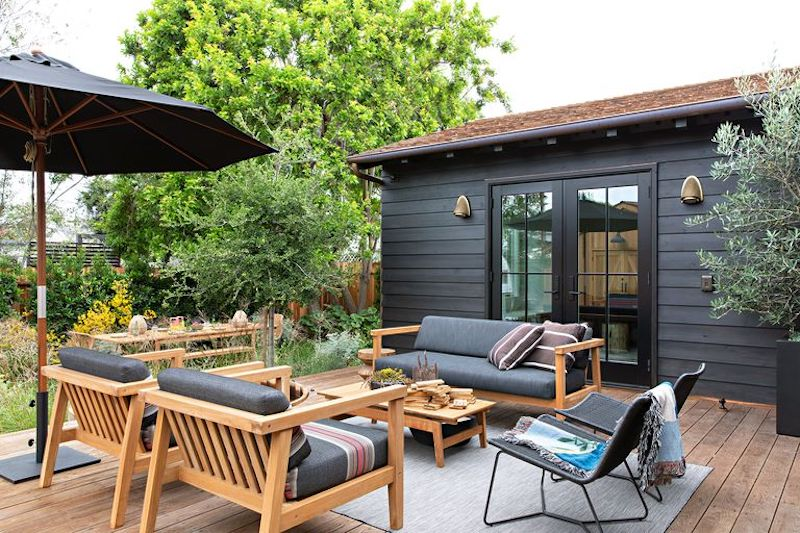 Pequeña terraza con tarima, muebles de madera y sombrilla con pie.