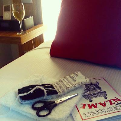 Bed in a hotel room with an NZAME magazine, a finished piece of knitting, scissors and a needle case on it. On the bedside table is a glass of wine and an iPod.