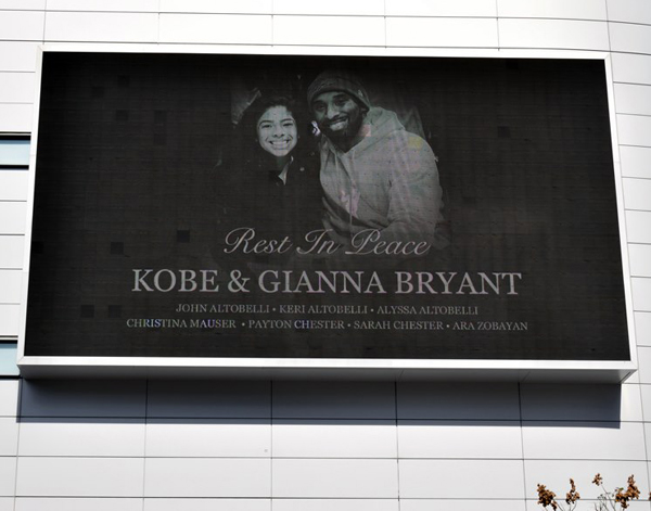 Kobe Bryant, his daughter Gigi and the seven other individuals who were aboard the helicopter that fateful day last year are honored on a large TV screen at L.A. Live...on January 27, 2020.