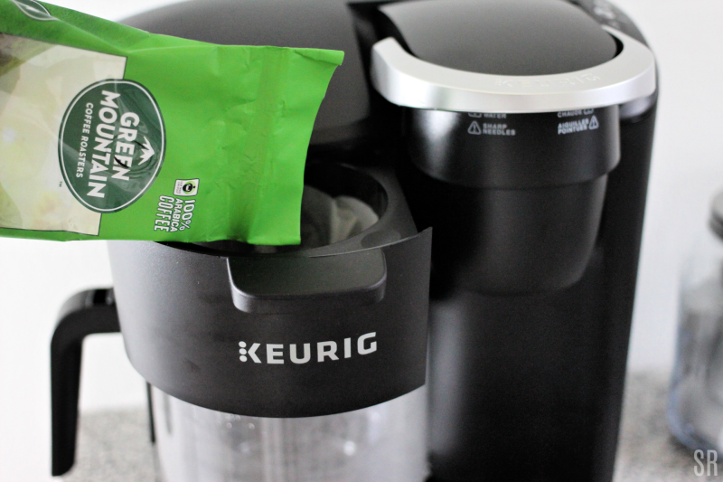 pouring coffee grounds into a Keurig Coffee maker