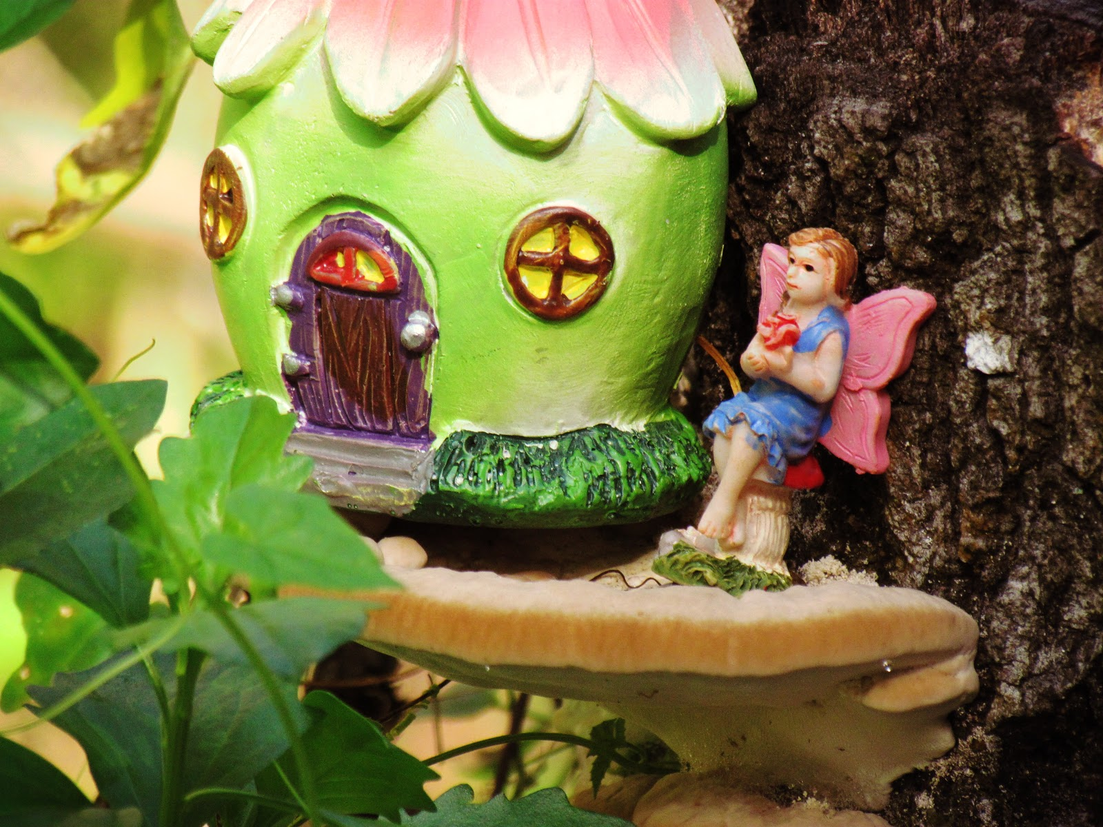 A fairy girl figurine with a flower dress living on a mushroom patio with a green fairy house on a hiking trail in Florida