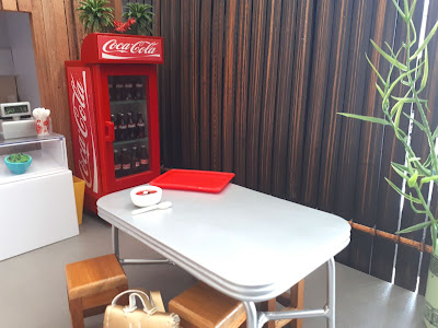 1/2 scale modern miniature asian cafe with a counter, drinks fridge, rustic fence with a bamboo plant in front of it and a metal table with a bowl of soup on it and wooden stool and a back pack in front of it.