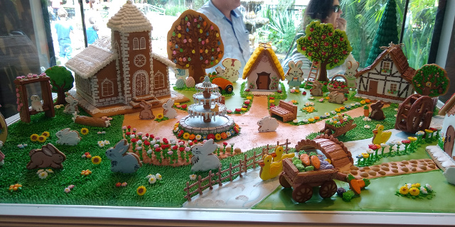 A church, houses, bunnies, ducks, trees and fountain made with cookies.