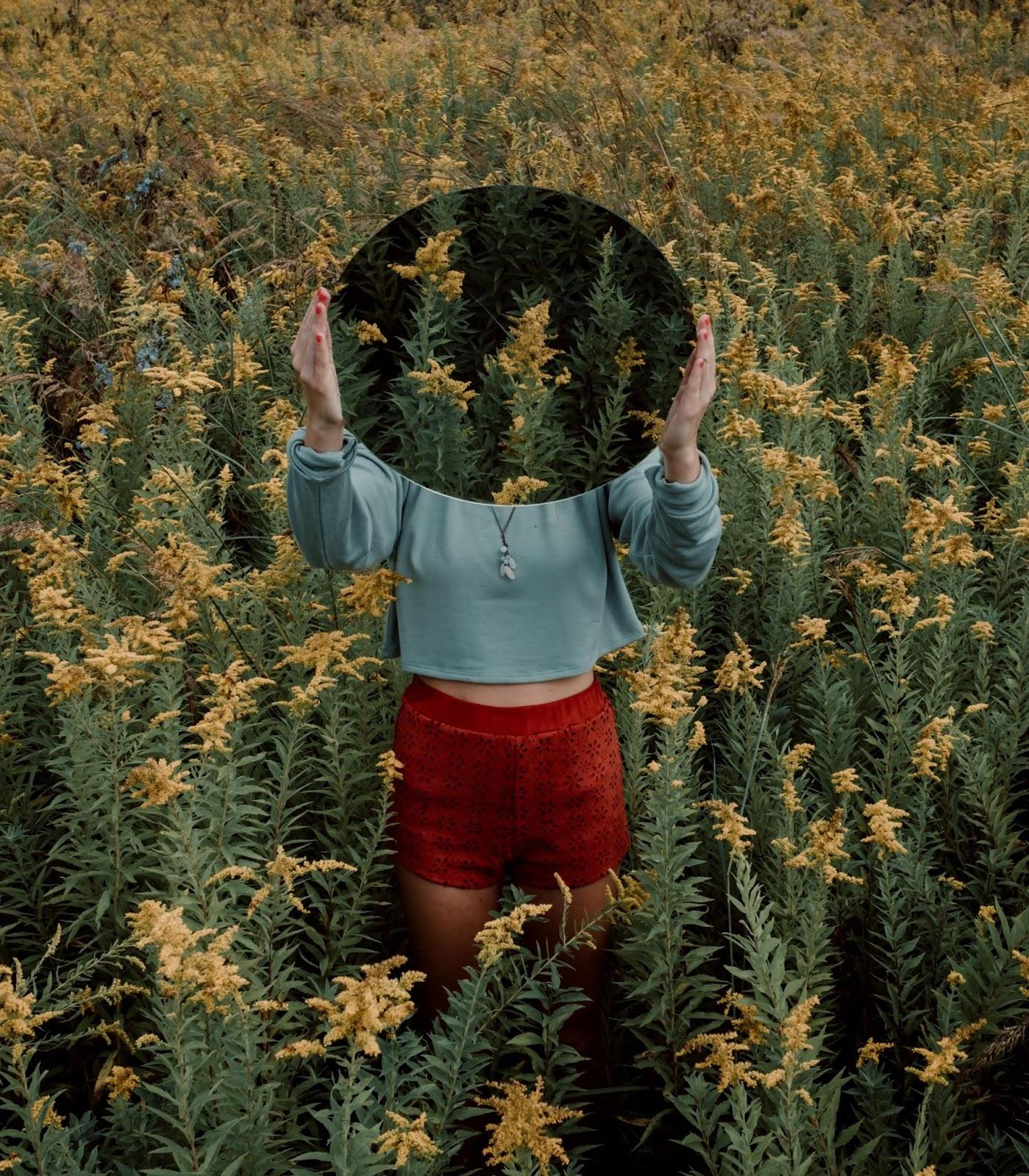 donna con specchio in mano in un campo di fiori