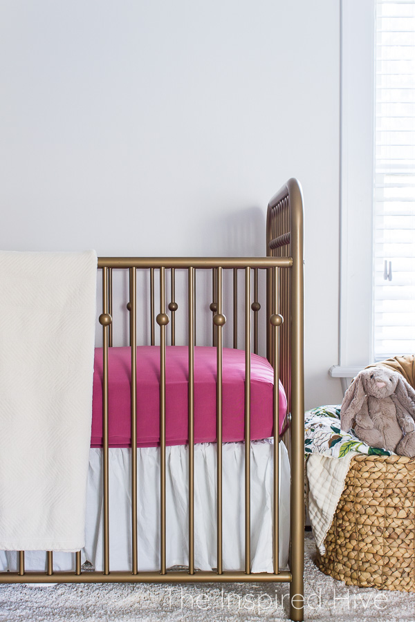 Gold crib, pink sheets, basket of stuffed animals, NatureSoft blanket