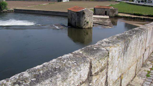 antigos moinhos num rio visto de uma ponte