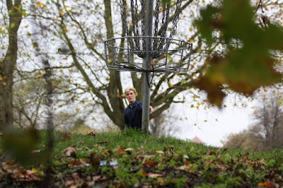 Photo shows Connor looking at a Disc Golf basket