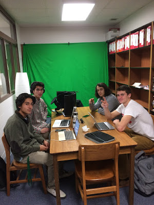 photo of kids working with laptops and greenscreen