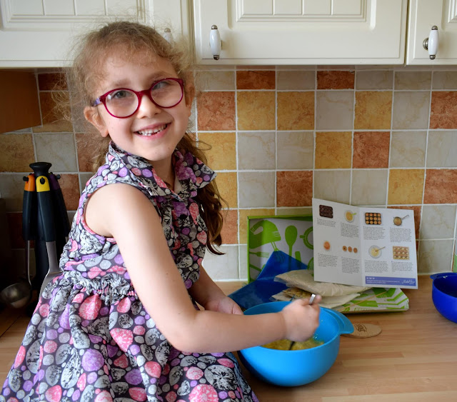 Small girl wearing glasses mixing a cake mix in a blue bowl.