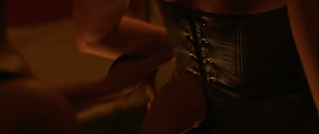 """Charles Guyette tight-lacing a corset in the film, """"Professor Marston and the Wonder Women,"""" with Olive Byrne as Wonder Woman"""