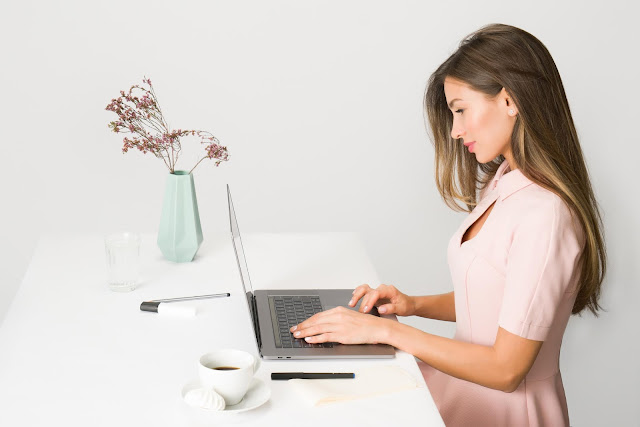 Brunette girl in pink working on a laptop.