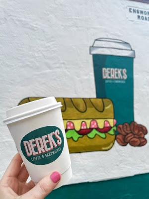 Derek's sandwich shop in Liverpool- coffee cup held up against mural.
