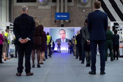 Matt Hancock on huge flatscreen overlooking rows ofNHS workers at the opening of one of the nightingale hospitals,