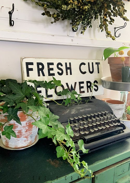Spring Home Tour - living room cabinet decor with plants and typewriter.