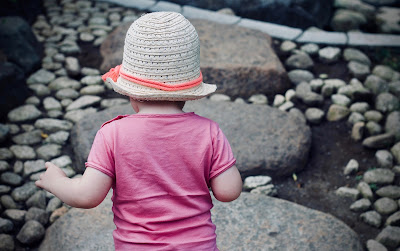 A little girl, viewed from behind, toddles through a rocky landscape