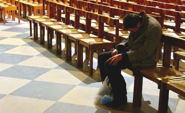A imagem mostra um homem mal vestido sentado sozinho em um banco de igreja com a cabeça baixa pedindo ajuda a Deus. ao lado do seu pé esquerdo vemos uma sacola com alguns pertences.