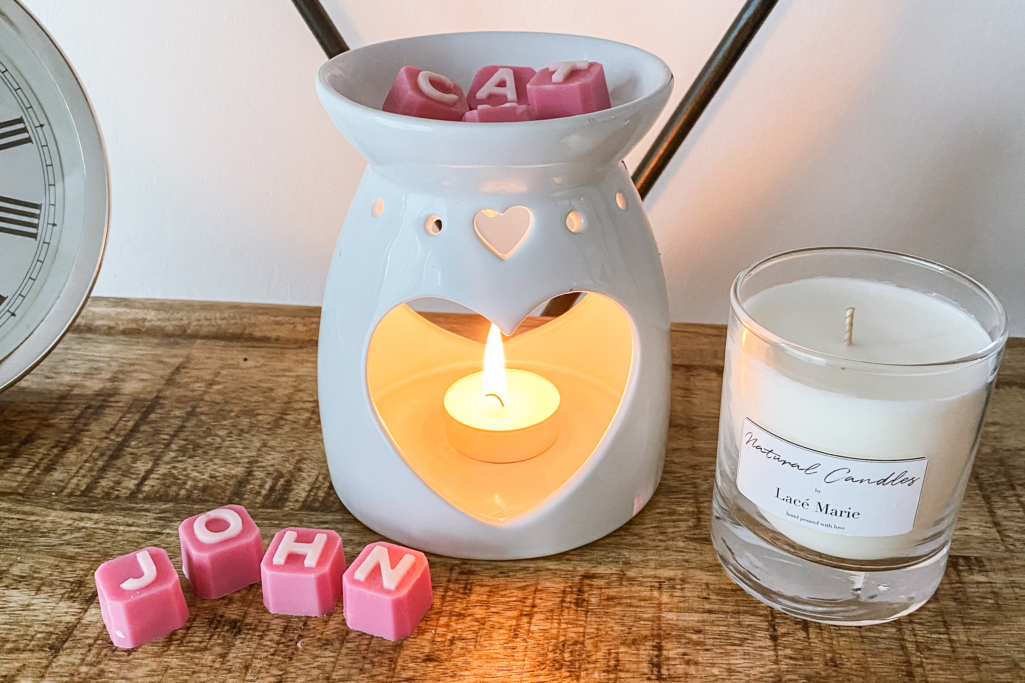 Wax melter with wax melts and a candle next to it.