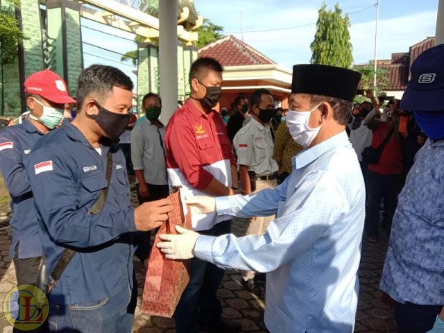 """Sebagai salah satu garda terdepan memberikan informasi mengenai Corona Virus atau Covid-19, wartawan yang bertugas di Lampung Utara mendapat bantuan Alat Pelindung Diri (APD) berupa masker dari Plt. Bupati Lampura H.Budi Utomo, Sabtu (18/4/2020). Selain memberikan masker kepada wartawan, Budi juga membagikan sembako kepada masyarakat Lampura yang terdampak Covid-19. Secara simbolis, pemberian APD kepada para wartawan diberikan langsung oleh Budi Utomo, di rumah dinasnya. """"Kegiatan kita hari ini selain membagikan masker kepada para wartawan, juga membagikan ke masyarakat untuk wilayah Pasar Kotabumi. Pembagian dilakukan di Pasar Central dan sepanjang Jalan Jendral Sudirman ini termasuk Pasar Decon juga,"""" ujarnya. Kemudian, untuk sembako dibagikan ke para pedagang yang biasa mencari nafkah di Tugu Payan Mas, yang terpaksa libur akibat dampak Covid-19. """"Oleh karena itu para pedagang yang terdampak otomatis penghasilan mereka hilang, maka dari itu kita memberikan bantuan kepada mereka untuk melanjutkan kebutuhan sehari-hari,"""" lanjutnya. Selain itu, Pemkab Lampura melalui Dinas Sosial sedang melakukan pendataan untuk pemberian bantuan langsung tunai oleh Kemensos. """"Kemudian untuk desa itu juga ada bantuan dari kementrian desa,ada 25-35% dana desa di peruntukan bantuan langsung tunai yang mungkin penyelenggaraan nya melalui rekening,"""" pungkasnya. Dalam pembagian APD tersebut turut hadir berbagai perwakilan organisasi pers yang ada di Kabupaten Lampung Utara."""