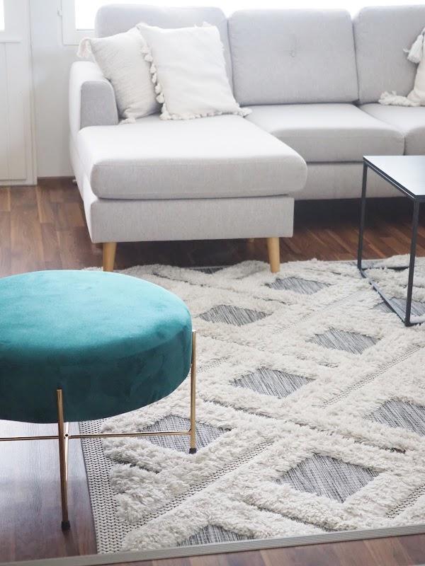 Beige sohva harmaan maton kanssa