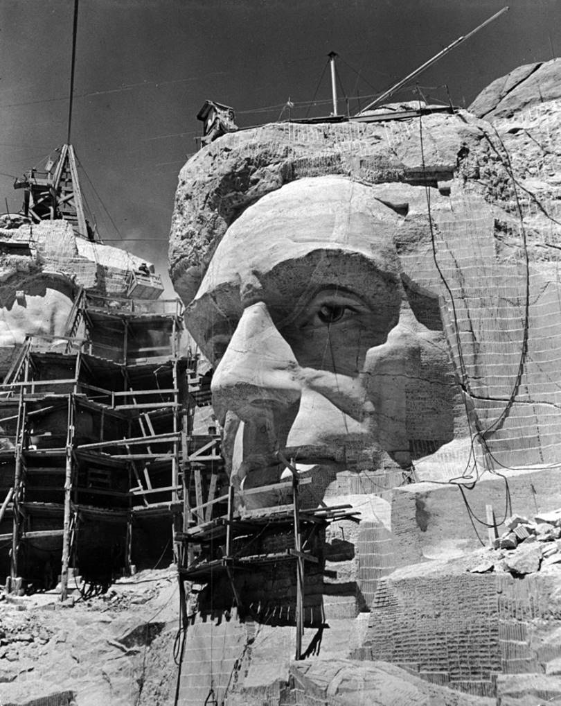 Scaffolding around a sculpture of Abraham Lincoln partially carved from a rock, circa 1941.