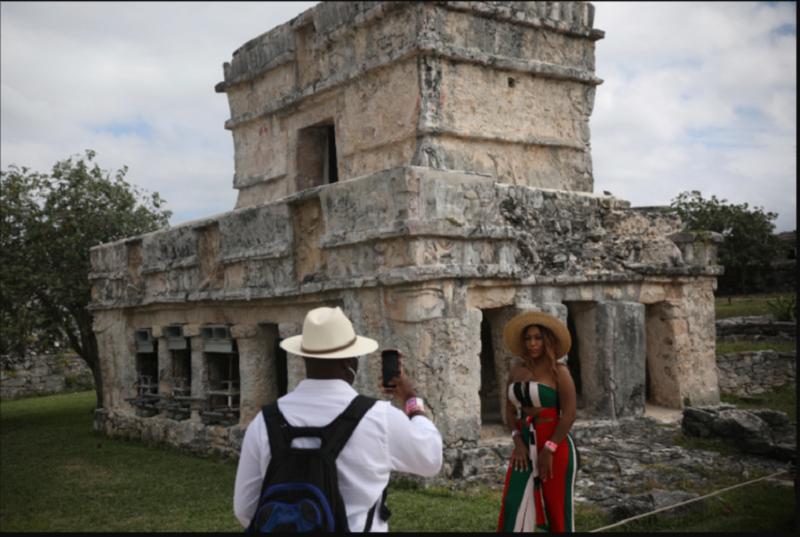 Un turista posa para una foto durante una visita a las ruinas mayas de Tulum en el estado de Quintana Roo, México, el martes 5 de febrero de 2021 / VOA