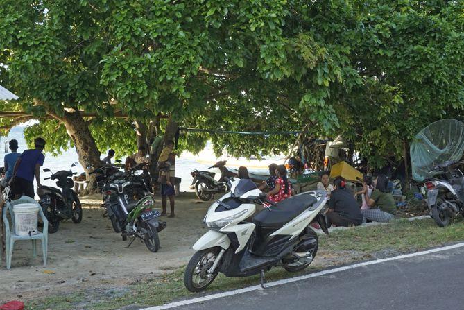 Masyarakat setempat bersantai di tepian  pantai