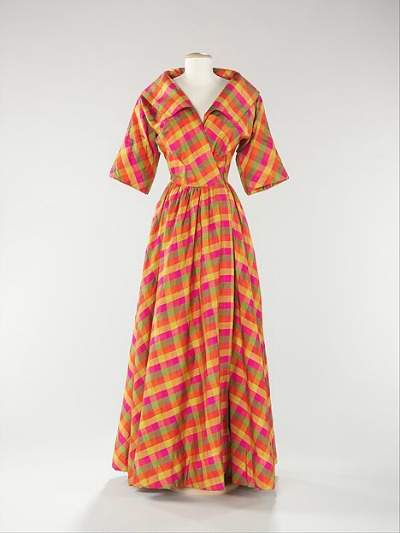 Evening dress by Bonnie Cashin in fuschia, orange, green, yellow plaid on display on dress stand
