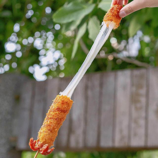 """Nền văn hóa ẩm thực Đài Loan nhận được sự ảnh hưởng và du nhập từ nhiều nơi. Và trong đó không thể thiếu những món ăn đến từ xứ sở kim chi Hàn Quốc như Hotdog Phô mai. Đây là một món ăn chiên xù dành riêng cho các tín đồ nghiện phô mai. Với phần dưới là xúc xích Đức kết hợp với phần trên tràn ngập phô mai morazella. Lớp vỏ chiên xù bên ngoài giòn rụm được rưới nước sốt với nhiều tầng hương vị nhất định sẽ """"đưa đẩy"""" bạn ngay từ những miếng cắn đầu tiên.    Vừa cắn nhẹ vỏ bánh, nhân phô mai sánh mịn, dẻo quẹo với mùi thơm dịu nhẹ đầy mê hoặc kết hợp với phần vỏ vàng giòn trong từng tầng hương vị nước sốt. Vừa nhai vừa xuýt xoa độ giòn béo đan xen một cách hài hoà."""