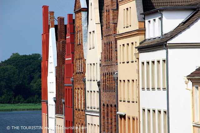 A row of olourful period facades next to a river.