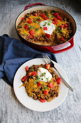 plate of one pan taco rice skillet meal topped with sour cream, tomatoes and cilantro in front of red cast iron skillet full of remaining dish