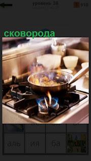 на плите стоит сковорода и готовится еда на огне