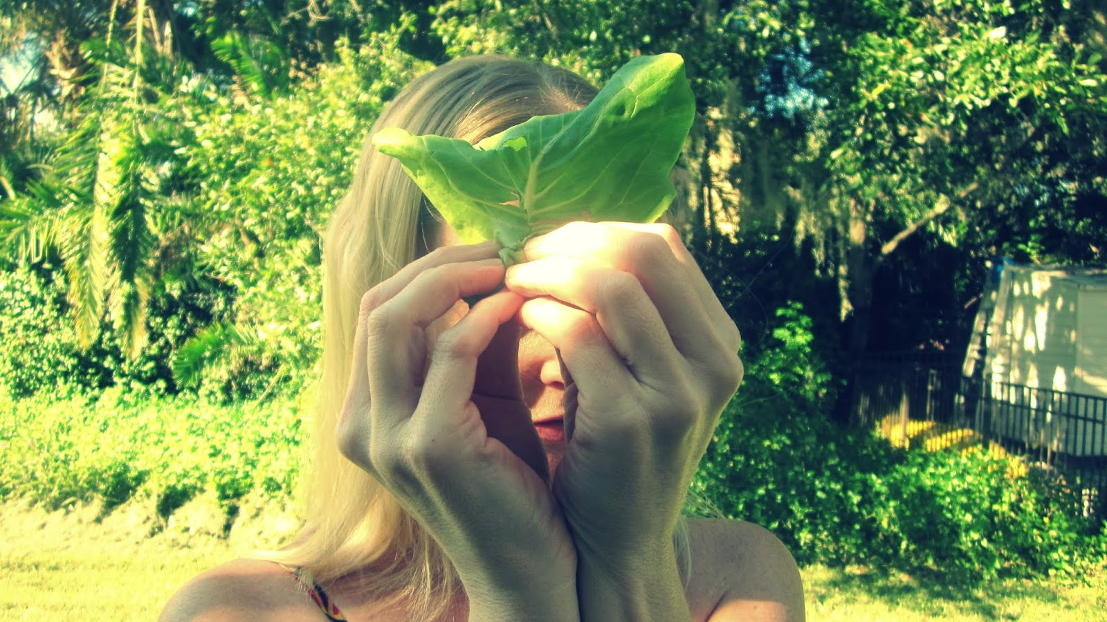 A blonde woman holding a butter lettuce leaf wrap over her eyes in the palm tree backdrop of a Florida Lifestyle