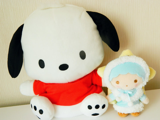 A photo showing two sanrio plushies, one of a puppy in a red shirt and the other of a blue-haired boy with a star