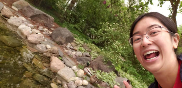 Han taking a selfie with a live ducks in a ornamental pond on campus