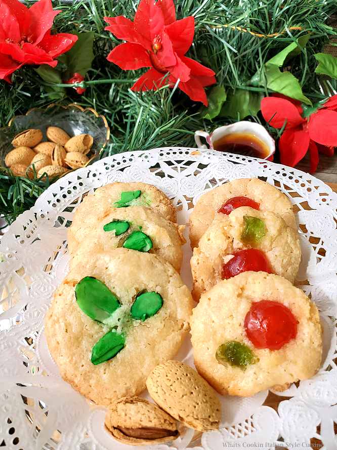 these are Italian cookies made with almond paste with green tinted almonds on top and some have candied red and green cherries for Christmas with nuts and black coffee in the background