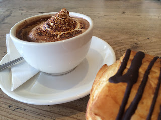 Cup of hot chocolate with toasted marshmallow floating in it. And a section of chocolate croissant visible on white saucer edge.