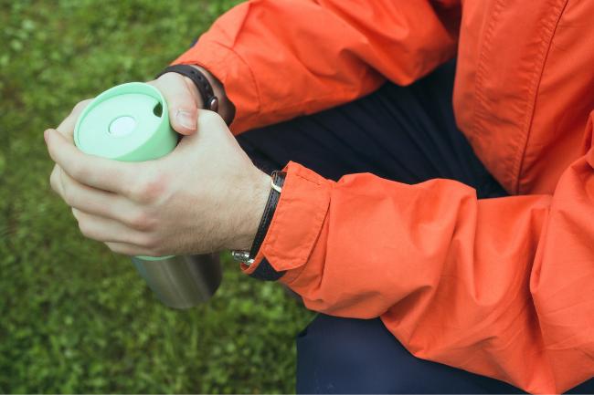 melhor copo termico sendo segurado por alguem com roupas de frio